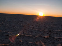 Słońce na wyginającym się horyzoncie nad piec, suszy krakingową skorupę Makgadikg Obraz Royalty Free