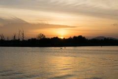 Słońce pójść puszek za lasem nad wodny chmurny, jest/ Zdjęcia Stock