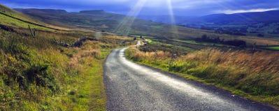 Słońce pęka przez chmury nad Crag Bocznej drogi Yorkshire doliny obrazy stock