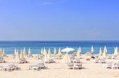 Słońce parasole na kurorcie i łóżka wyrzucać na brzeg przeciw błękitnemu morzu i jasnemu niebu na jaskrawym słonecznym dniu Plażo Zdjęcie Royalty Free