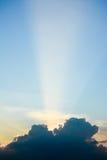 Słońce promienia połysk przez zmrok chmury w wschodu słońca niebie Obrazy Royalty Free