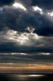 Słońce promienie łama przez chmur i iluminujący powierzchnia morze Obrazy Royalty Free