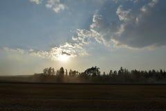 Słońce promienie błyszczą od chmur nad polem dokąd żniwiarz ciie Czas żniwa latania pył od syndykatów żniwiarzów Fotografia Royalty Free