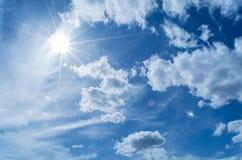 Słońce promienie przeciw niebieskiemu niebu w chmurach, obraz stock