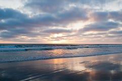 Słońce ustawia nad oceanem spokojnym widzieć od plaży zdjęcie royalty free