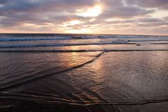 Słońce ustawia nad oceanem spokojnym widzieć od plaży obraz royalty free
