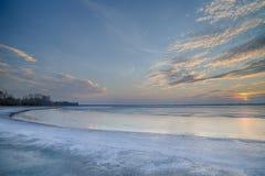 Słońce ustawiający nad zamarzniętym jeziorem Obraz Stock