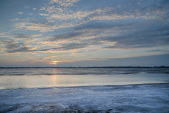 Słońce ustawiający nad zamarzniętym jeziorem Obrazy Stock