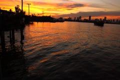 Słońce ustawiający przy rzeką i miasta tłem Obraz Stock