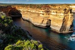 Słońce zaświecał piaskowcowe falezy przeciw ciemnemu oceanowi przy Dwanaście apostołami, Wielka ocean droga, Wiktoria, Australia fotografia royalty free