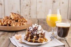 Słodcy Belgijscy gofry dla śniadania, dekorujący z białą śmietanką i czekoladowym kumberlandem Szkło z kawowym czernią i sokiem p obrazy stock