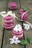Słodcy ciemnopąsowi francuscy macaroons z hiacyntowymi kwiatami i mennicą na ciemnym drewnianym tle obrazy stock