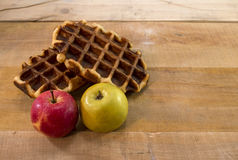 Słodcy gofry i jabłka na biurku Zdjęcia Stock