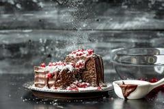 Słodcy momenty nalewali punkty gorącą, ciekłą czekoladę, kropiącą z czerwonymi granatowów ziarnami i sproszkowanym cukierem - sło fotografia stock