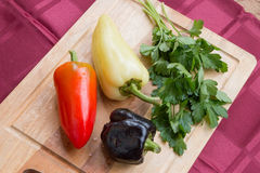 Słodcy pieprze różni kolory i wiązka pietruszka na drewnianej desce Zdjęcia Stock