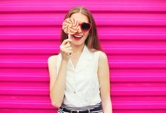 Słodka ładna młoda kobieta ma zabawę z lizakiem nad menchiami Fotografia Royalty Free