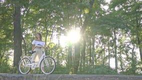 Słodka brunetka w białej spódnicie, bluzka stacza się w świetle słonecznym białego miasto rower wzdłuż ścieżki w parku i zbiory wideo