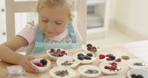 Słodka bułeczka filiżanki przygotowywa małą dziewczynką zbiory