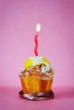Słodka bułeczka z jeden płonącą świeczką Zdjęcie Royalty Free
