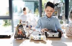 Słodka chłopiec egzamininuje frontową część mechaniczny pojazd Zdjęcia Stock