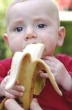 Słodka chłopiec je banana zdjęcia stock