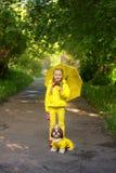 Słodka dziewczyna chodzi w parku w żółtej kurtce pod parasolem z psami obraz royalty free