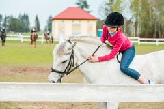 Słodka dziewczyna jedzie białego konia, atleta angażował w equestrian sportach, dziewczyny uściśnięciach i buziakach, koń Zdjęcie Stock