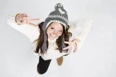 Słodka dziewczyna odziewa śmiać się w chłodno zimie, robi zwycięstwo znakowi Obraz Stock