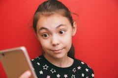 Słodka dziewczyna patrzeje urządzenie przenośne na czerwonym tle zaskakiwał spojrzenie zdjęcia stock