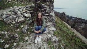 Słodka dziewczyna siedzi resztkami ściana stary forteca na wzgórzu morzem zbiory wideo
