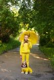 Słodka dziewczyna w żółtej kurtce pod parasolem z psim odprowadzeniem w pa zdjęcia royalty free