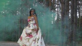 Słodka dziewczyna w sukni chodzi w koloru dymu przeciw tłu las zdjęcie wideo