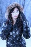Słodka dziewczyna z zimą odziewa pod opadem śniegu obrazy royalty free