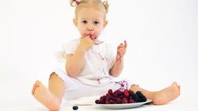 Słodka dziewczynka jedząca świeże jagody na białym tle zbiory