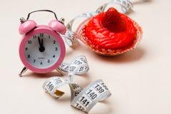 Słodka karmowa pomiarowa taśma i zegar na stole Zdjęcie Royalty Free