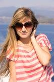 Słodka młoda blondynki dziewczyna uśmiechnięta i przyglądająca obrazy royalty free