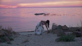 Słodka młoda dziewczyna w długiej sukni chodzi wzdłuż banka rzeka zbiory