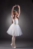 Słodka mała balerina pozuje na szarym tle Zdjęcia Stock