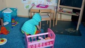 Słodka mała berbeć dziewczyna kłaść puszka dziecka - lala w zabawkarską łóżkową pokrywę z koc zdjęcie wideo