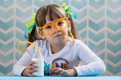 Słodka mała dziewczynka pije mleko z śmiesznymi szkłami słomianymi obraz royalty free