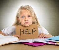 Słodka mała szkolna dziewczyny mienia pomoc podpisywać wewnątrz stres z książkami Obrazy Stock