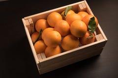 Słodka pomarańcze w drewnianym pudełku odizolowywającym na czarnym tle Zdjęcie Royalty Free