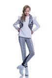 Słodka rozochocona nastoletnia dziewczyna jest ubranym dziającą kamizelkę, spodnia i nowożytnych buty odizolowywających na białym Fotografia Royalty Free