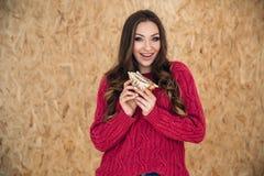 Słodka, rozochocona Przyglądająca dziewczyna ubierająca w eleganckiej ciepłej kurtce, iść jeść jej kanapkę z contentment zdjęcia royalty free