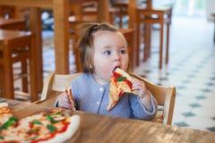 Słodka urocza dziecko dziewczynki łasowania pizza przy restauracją zdjęcie stock
