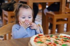 Słodka urocza dziecko dziewczynki łasowania pizza przy restauracją fotografia royalty free