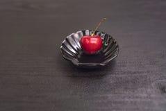 Słodka wiśnia w czarnej skorupie na czerń stole Zdjęcie Royalty Free