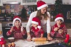 Słodki berbecia dziecko i jego stary brat, chłopiec, pomaga mamusi narządzania Bożenarodzeniowi ciastka w domu fotografia royalty free