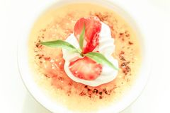 Słodki creme brulee z świeżą truskawką na białej filiżance, zamazany biały tło Odgórny widok, zamyka up Selekcyjna ostrość Wysoki zdjęcie royalty free