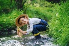 Słodki dziecko, bawić się na małej rzece z kaczątkami Obrazy Stock